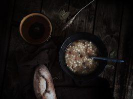 Una foto de un cuenco con sopa de restos al lado de un pan pequeño