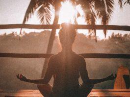 una chica en posición de loto frente al sol naciente